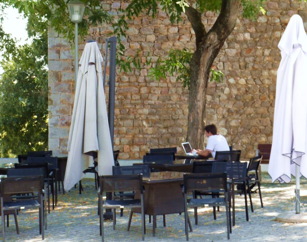 Tavira, Algarve, Portugal. Digital nomad at cafe in a fortress