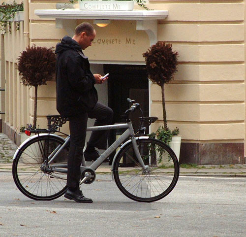Copenhagen, Denmark. cyclist has stopped to send a text message on his phone.
