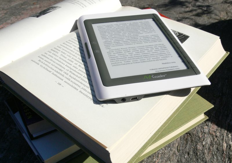 ereader on top of paper book stack in sunshine