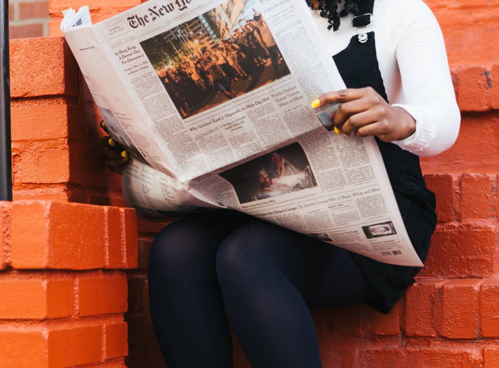 woman reading new york times newspaper on stairs. photo by the creative exhcange at unsplash.