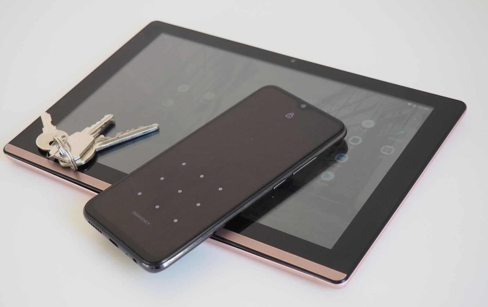 tablet and phone on table, house keys on tablet screen